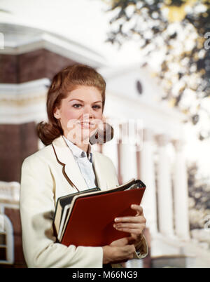 1960 SMILING COLLEGE GIRL COED HOLDING BOOKS IN FRONT OF CAMPUS BUILDING LOOKING AT CAMERA - KS3862 HAR001 FLIP Banque D'Images