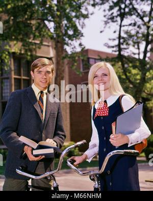 1960 PORTRAIT COUPLE D'ÉTUDIANTS SUR LE CAMPUS avec des vélos et des livres photo - KS5711 HAR001 JOIE HARS CAMPUS Banque D'Images
