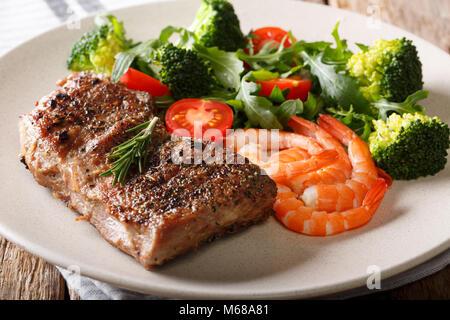 Terre et mer. Pavé de boeuf avec légumes frais et crevettes royale close-up sur une plaque sur une table. L'horizontale Banque D'Images