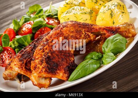 Cuisses de poulet rôti avec des pommes de terre et légumes grillés Banque D'Images