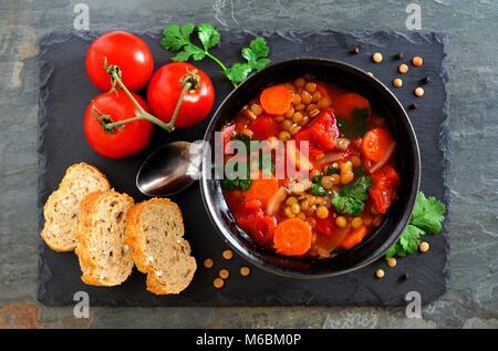 Des tomates, soupe de lentilles, les frais généraux, scène télévision déposer sur un fond ardoise foncé Banque D'Images