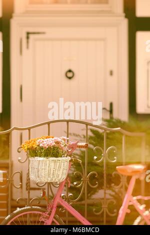 Vélo rose bye permanent la clôture avec porte blanche en arrière-plan, couleurs vintage Banque D'Images