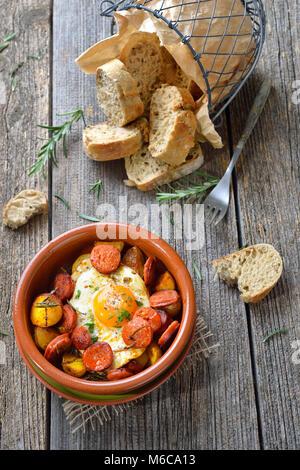 L'Espagnol tapa: chorizo saucisse avec œuf frit et bébé pommes servi dans une cazuela en terre cuite lave Banque D'Images