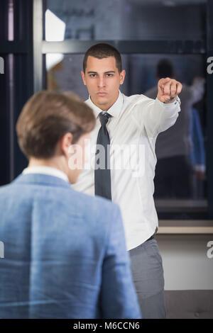 Travailleur tir exécutif en faisant remarquer avec son index pour sortir du bureau. Banque D'Images