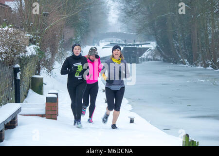 Les coureurs le long du canal gelé à Atherstone, Coventry North Warwickshire, Royaume-Uni. Crédit : David Warren/Alamy Banque D'Images