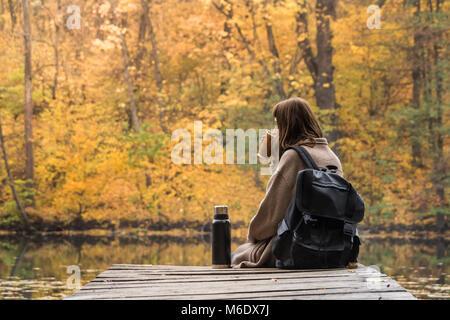Girl reste et boisson chaude de thermos près du lac dans un parc de la nature sur un jour d'automne d'or Banque D'Images