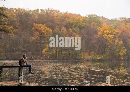 Girl bénéficie d'reste et boit du café près du lac au parc de la nature de l'or moelleux jour d'automne Banque D'Images