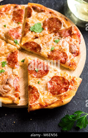 - Pizza au Pepperoni pizza maison avec pepperoni, fromage et sauce tomate sur fond rustique en pierre noire avec Banque D'Images
