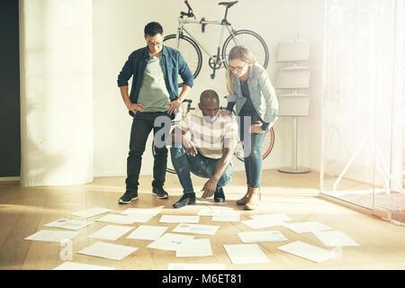 Trois collègues de travail debout dans un bureau moderne et élégante de la paperasserie de lecture portant sur le Banque D'Images