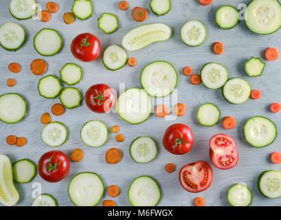 Couper les légumes sur fond de bois. Vue de dessus de concombres, tomates, courgettes, carottes. Banque D'Images