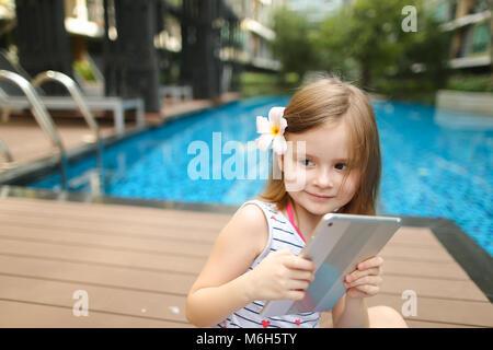 Petit enfant en tenant sur tablet selfies assis près de natation poo