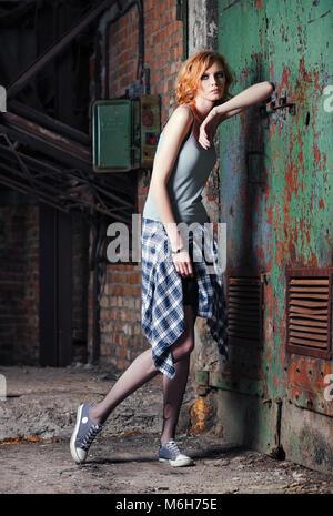 Portrait d'une belle jeune fille grunge (rock) en chemise à carreaux et collants déchirés Banque D'Images
