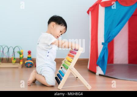 Bébé garçon asiatique apprend à compter. Mignon enfant jouant avec abacus jouet. Petit garçon s'amusant à l'intérieur Banque D'Images