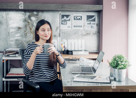 Asian businesswoman prendre une pause-café après avoir travaillé avec visage souriant, heureux de la vie de bureau Banque D'Images