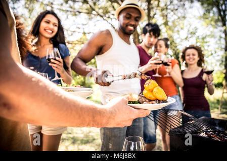 Groupe d'amis faire un barbecue dans la nature. La consommation et le partage des émotions positives Banque D'Images