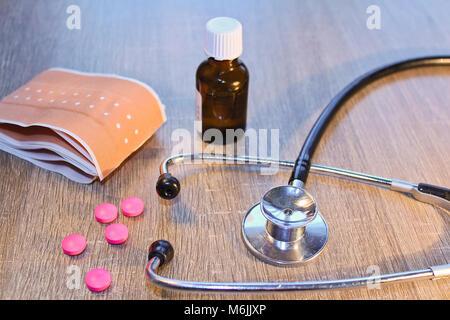 Stéthoscope, comprimé et bandage sur fond de bois, concept médical Banque D'Images