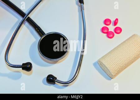 Stéthoscope, comprimé et bandage sur fond blanc, concept médical Banque D'Images