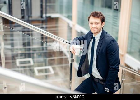 Homme confiant holding Coffee cup et à l'aide de son téléphone intelligent tout en marchant dans le hall Banque D'Images