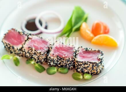 Le thon grillé aux graines de sésame avec salade verte on white plate Banque D'Images