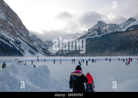 Les enfants et les familles le patinage sur glace et de jouer au hockey sur étang Lake Louise, Banff National Park, Banque D'Images