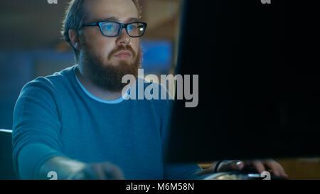 L'accent jeune homme travaille sur un ordinateur personnel. Il porte des lunettes et a Barbe, il travaille tard dans la nuit dans l'espace loft Bureau.