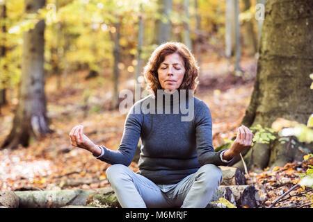 Senior woman meditating dans une forêt d'automne. Banque D'Images