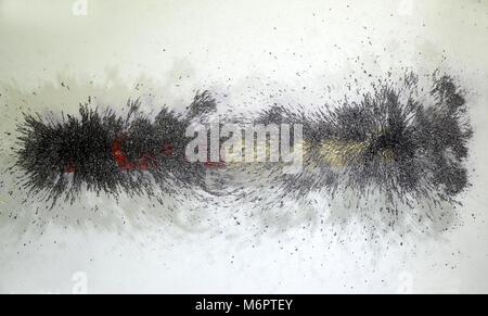 Les lignes de forces autour d'un aimant illustré, avec le fer jetons répartis sur une plaque de verre qui repose Banque D'Images