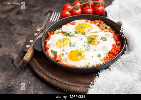 Shakshuka sains et savoureux dans une poêle. Oeufs au plat avec tomates, poivrons, légumes et fines herbes. Plat Banque D'Images