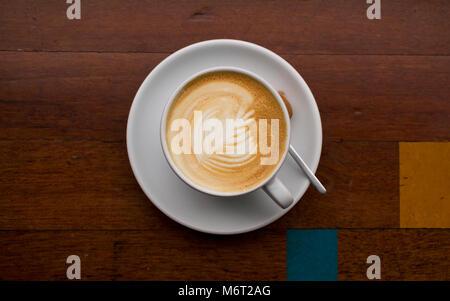 Latte art sur une table basse en bois avec un géométrique bleu et jaune détail carré Banque D'Images