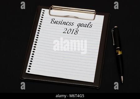 Vue de dessus du presse-papiers et feuille blanche avec les objectifs de l'écrit 2018 sur fond noir. Concept d'entreprise. Banque D'Images