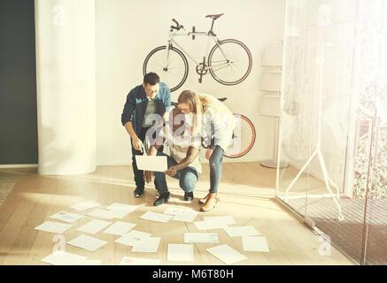 Trois collègues debout dans cool moderne bureau documents lecture pose sur le sol en face d'eux Banque D'Images