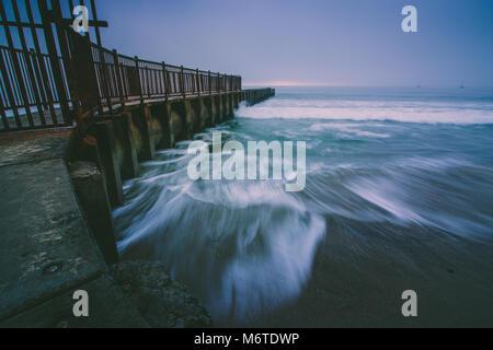 L'exposition longue photo de vagues se brisant sur la plage de McGurk jetée sur un jour brumeux au crépuscule, les Banque D'Images