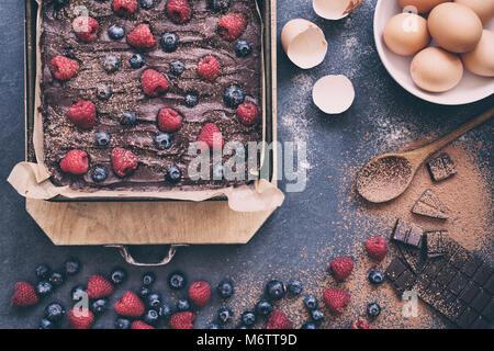 Des matières chocolat-framboise et bleuet mélange brownie dans une plaque à pâtisserie avec des ingrédients sur Banque D'Images