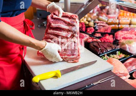 Coupe femme boucher morceau de viande de côtes dans sa boutique avec un couteau Banque D'Images