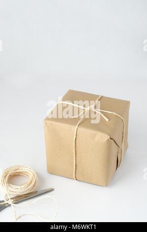 Une parcelle, enveloppés dans du papier brun et liés avec de la ficelle. Chaîne restants et ciseaux fermés se trouvent Banque D'Images