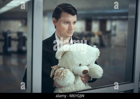 Jeune homme regarde par la fenêtre et sourit. Il a un ours en peluche dans ses mains Banque D'Images