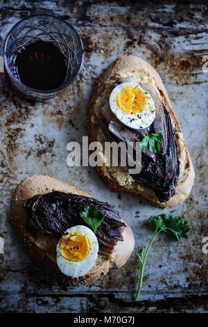 La chicorée rouge braisé crostini avec hoummos, oeuf mollet et épices Banque D'Images