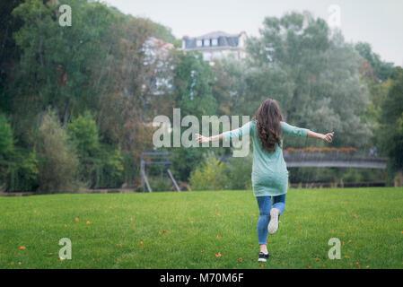 Jeune femme brune, habillé décontracté, exécutant heureux dans la pluie avec ses bras large, entouré d'herbe verte Banque D'Images