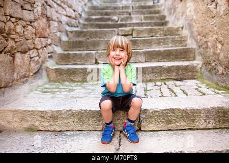 Cute smiling blonde petit garçon assis sur de vieux escaliers pavés avec les mains sur les joues, dans le centre historique de Rovinj