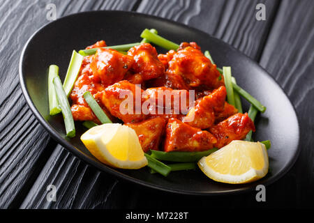 Morceaux de poulet en sauce rouge avec l'oignon vert et citron close-up sur une plaque sur une table horizontale. Banque D'Images