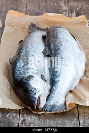 Gros plan sur un fond de bois, des saumons cru entier Banque D'Images