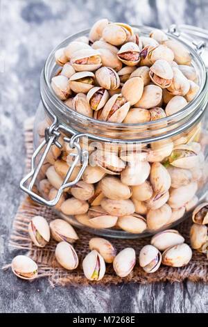 Les pistaches dans le bocal en verre sur la table en bois Banque D'Images