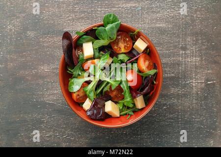 Salade de légumes frais du printemps avec tomates, fromage et mélanger les feuilles de roquette, Laitue niçoise, Banque D'Images