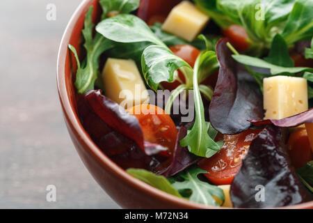 Plan Macro sur le bol avec une salade de légumes frais du printemps avec tomates, fromage et mélanger les feuilles Banque D'Images
