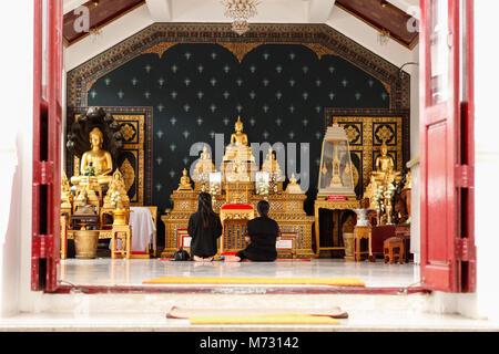 Deux femmes dans des vêtements noirs assis à prier à l'intérieur d'un temple du Grand Palais à Bangkok, en face Banque D'Images