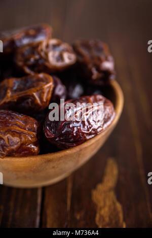 Dates fraîches Fruits au bol en bois sur fond de bois Banque D'Images