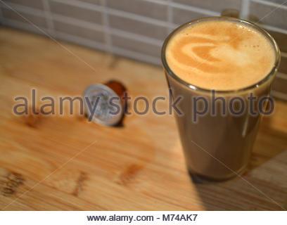 Gros plan du café blanc dans grand verre de lait et de mousse. Dosette sur table en bois à côté de verre Banque D'Images