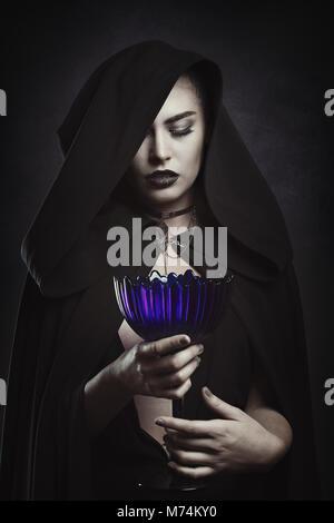 Belle vampire avec une coupe rituelle. La figure à capuchon Banque D'Images