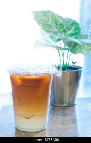 Thai thé et lait frais mélangé avec de la glace dans le godet en plastique au coffee shop en Thaïlande prêt à servir les clients. Thé Thaï glace est célèbre et populaire co
