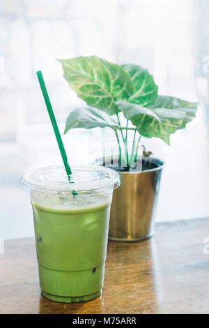 Le thé vert matcha et le lait frais mélangé avec de la glace dans le godet en plastique au coffee shop en Thaïlande prêt à servir les clients. Thé vert glacé Latte est famou